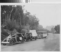 Automobiles and bus decorated for celebration of newly opened highway, Palos...